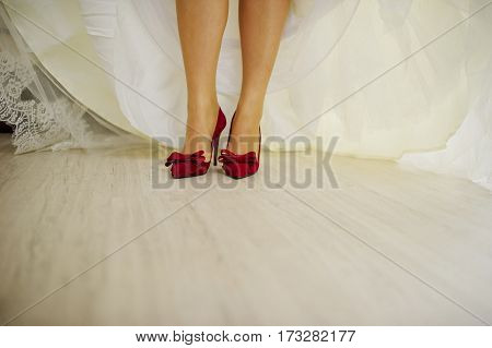 Red Velvet Shoes On Legs Of Bride.