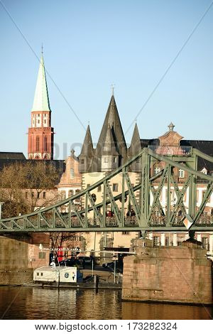 The bridge Iron Bridge and the Tower of St. Nicholas Church and other historic buildings of the Old Town in Frankfurt.