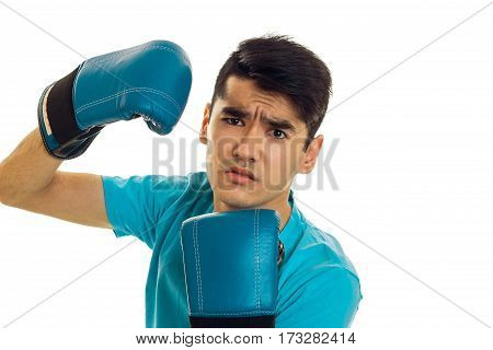 young serious guy in blue boxing gloves is isolated on a white background