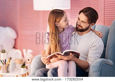 Lets read. Attentive bearded man wearing white jumper embracing his daughter while holding book in left hand