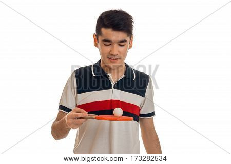 young guy holds itself the racket for tennis and looking down isolated on white background