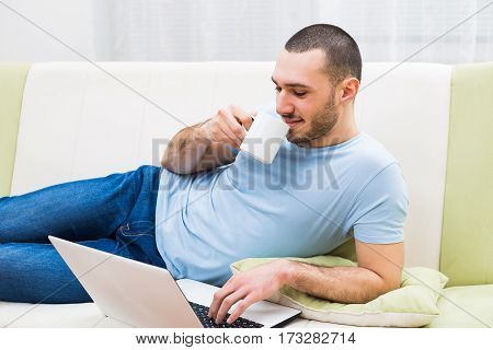 Man using laptop and drinking coffee at his home.
