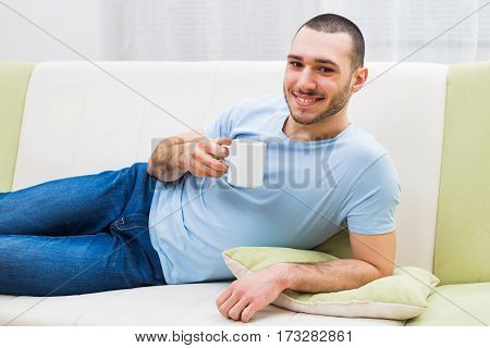 Young man enjoys drinking coffee at his home.