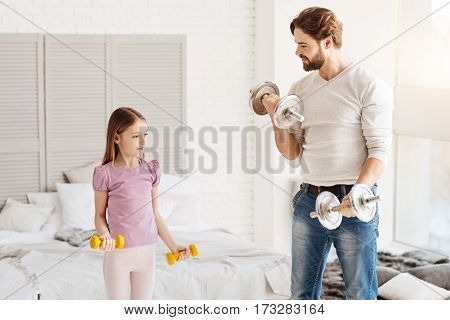 Time for sport. Serious little girl wearing violet tee shirt holding yellow dumbbells looking at father