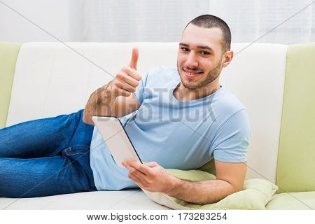 Man using digital tablet  and showing thumb up at his home.