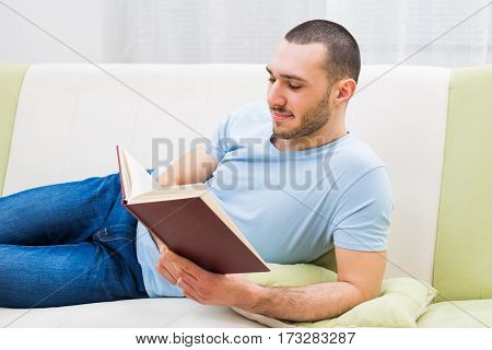 Man enjoys reading book  at his home.