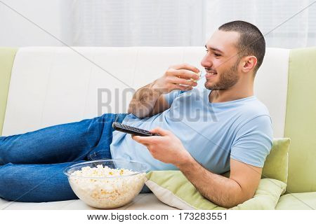 Man watching tv and eating popcorn at his home.