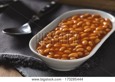 Baked white beans with tomato sauce served in a small bowl.