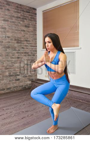 Young attractive woman exercise yoga indoors, trying to balance on just one leg with joined hands.