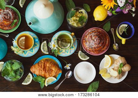 Cups Of Herbal Tea With Lemon And Mint Leaves, Ginger Root And Croissant On The Wooden Background, T