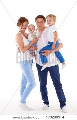 Young parents with sweet  children stand on a white background. Happy family. Six month and four years.
