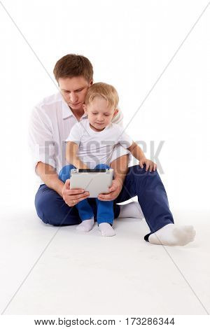 Young father and little son with computer tablet sit on a white background. Happy family. Parenting and early development.