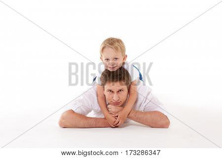 Young happy father with sweet child lie on a white background. Happy family.