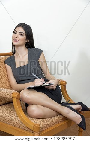 Business Woman Sitting On An Arm Chair.