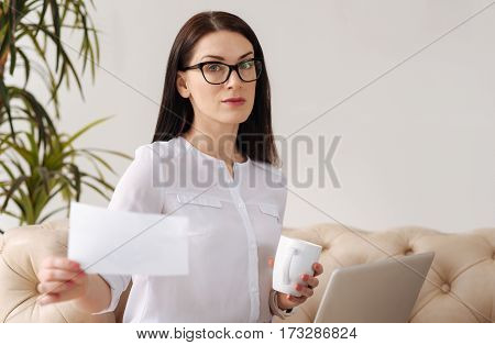 Typical workdays. Pleasant pretty serious woman wearing glasses and looking at the sheet of paper while working in the office