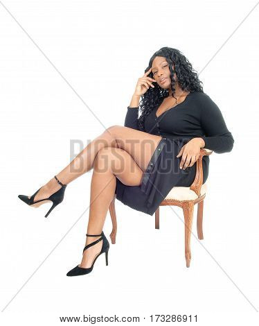 A beautiful African American business woman sitting in a jacket and heels isolated for white background.