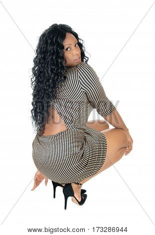 A beautiful African American woman in a short dress and long curly black hair crouching from the back isolated for white background.