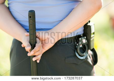 hands of the police officer holding a baton tonfa close up