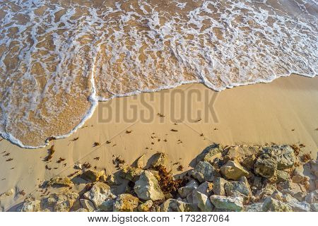 Breaking wave on a sandy beach with rocks