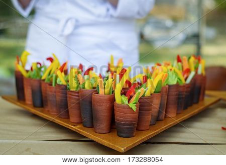 bright straw cutting fresh vegetables for buffet served in a clay cup