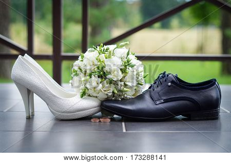 Wedding still life of a bouquet of white roses and white women's shoes and men's shoes black