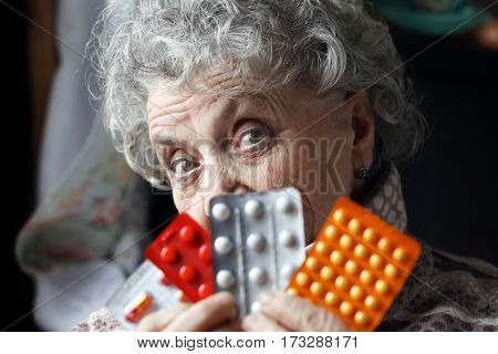 Old woman with pills on a dark background
