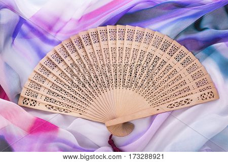 Beautiful wooden fan on the background of bright silk