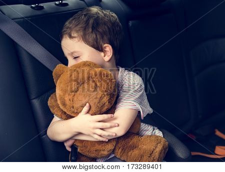 Little boy tired and sleeping hug teddybear in a car