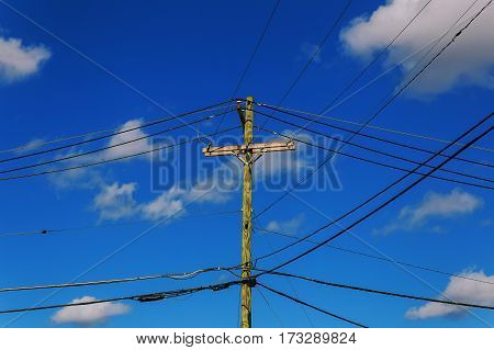 Old electricity post against blue sky with cloud, chaotic wire with nest on pole electric pole with wires against the sky clouds