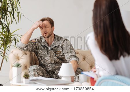 Unpleasant memories. Unhappy bearded military man holding his forehead and closing eyes while having unpleasant memories