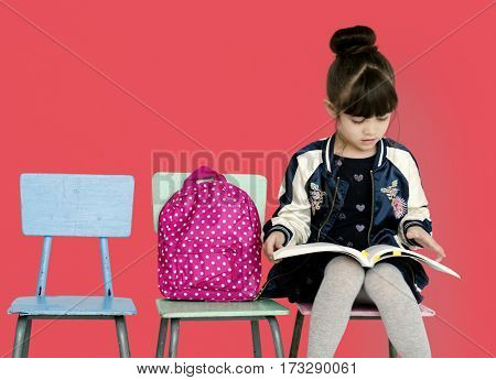 A little girl is reading a book