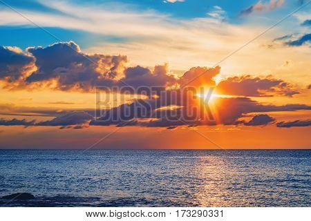 The sun's rays breaking through the clouds during the tropical bright sunset. Beautiful seascape with sea and rock in Nang Thong Beach, Khao Lak, Thailand.