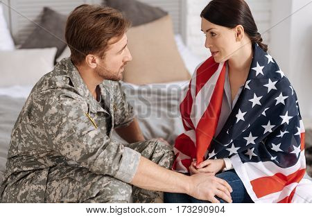 US army. Nice attractive brunette woman being wrapped in the us flag and looking at her husband while supporting him