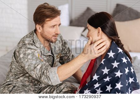 Do not want to leave you. Sad unhappy military man looking at his wife and holding her cheek while sitting on the bed