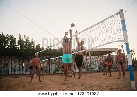 Male Caucasians, Arabs, Africans Playing Volleyball On The Beach At Sunset. Egypt. Hurghada. Golden