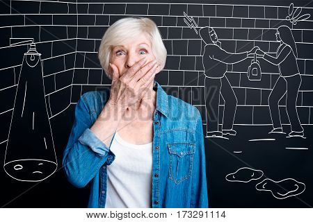 City crime. Shocked scared aged woman covering her mouth and trying to be quiet while witnessing the robbery