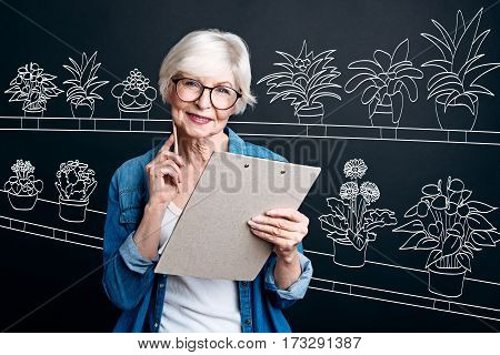 Flower delivery. Positive nice aged woman wearing glasses and holding notes while working in the flower shop