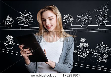Modern technology. Delighted pretty young woman holding a tablet and working with it while being in the flower shop