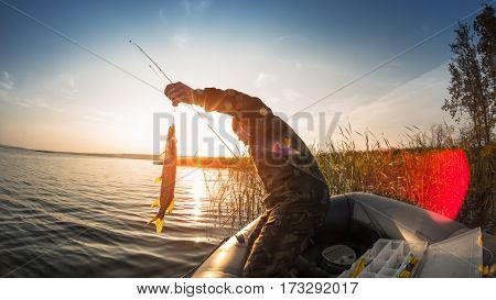 Man with fish in the boat on the lake at sunset