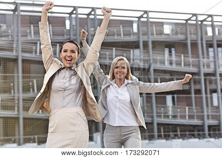 Excited young businesswomen with arms raised against office building