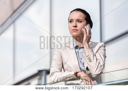 Serious young businesswoman using cell phone at office railing
