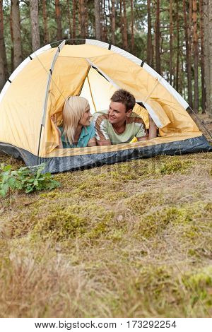 Romantic young couple camping in forest