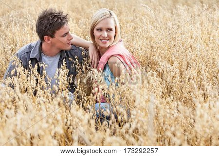 Beautiful young woman looking away while sitting with boyfriend amidst field
