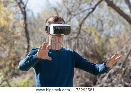 Young man wearing virtual reality glasses standing in a park