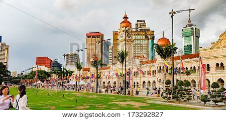Kuala Lumpur, Malaysia - February 7, 2016: Bangunan Sultan Abdul Samad located along Jalan Raja in front of Independence Square. Asian tourists making selfie photo on smartphon in the foreground