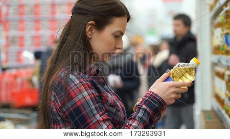 woman buys sunflower oil in supermarket or store