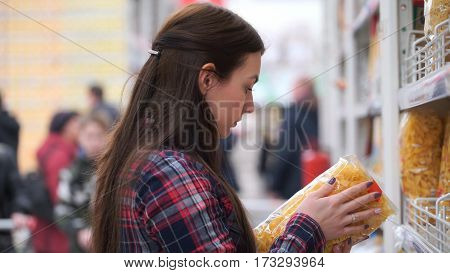 woman buys pasta in supermarket or store