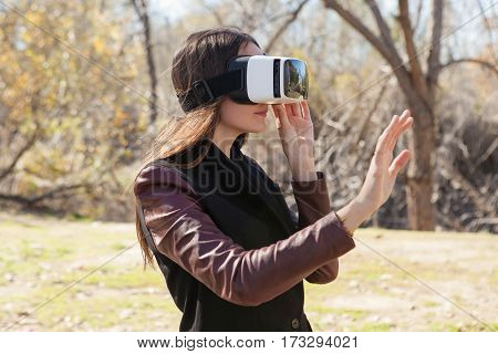 Young woman wearing reality glasses for mobile gaming applications in a park
