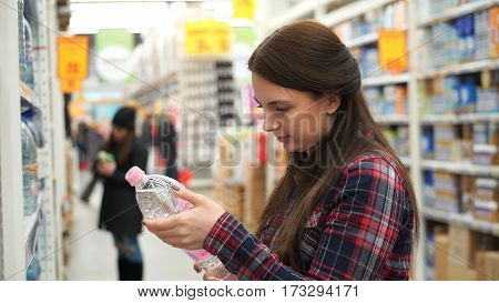 woman buys mineral water in supermarket or store