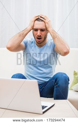 Young man sitting at sofa and in panic using laptop.